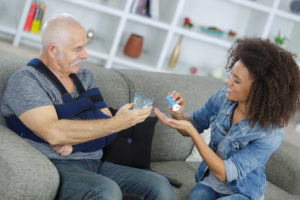 Woman Helps Man Take Medicine