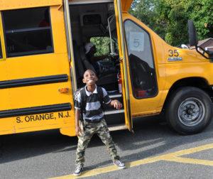 Smiling Kid In Front of School Bus